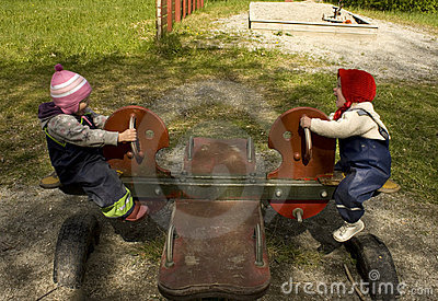 Two kids playing on a teeter totter