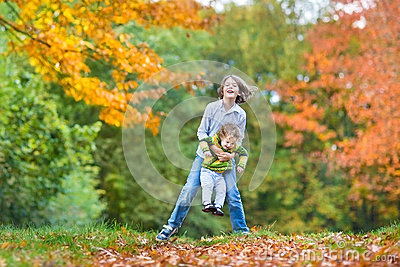 Two kids playing togeter in autumn park