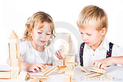 Two kids playing with wooden blocks indoor