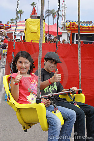 Two Kids Riding a Ride at the Fair or Carnival