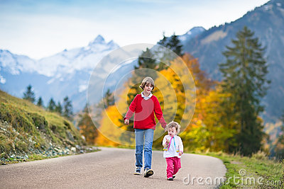Two kids on road between snow covered mountains