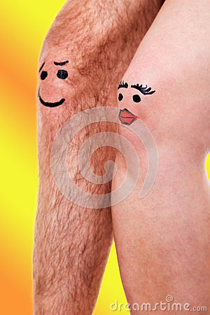 Two knees with funny faces in front of yellow background