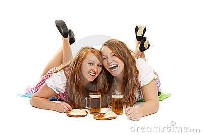 Two laughing bavarian girls with beer and pretzels