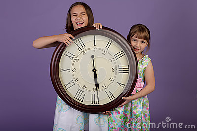 Two laughing girls holding a large wall clock