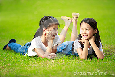 Two little asian girls laying on the green grass