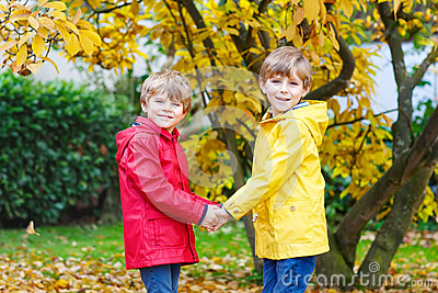 Two little best friends and kids boys autumn park in colorful clothes. Stock Photo