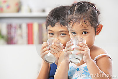 Two little boy and girl drinking milk
