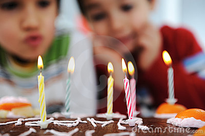 Two little boys blowing candles