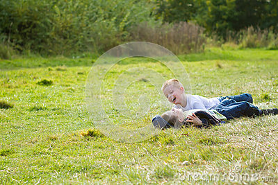 Two little boys playing in a grass field