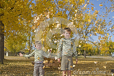 Two little boys throw colorful leaves in air