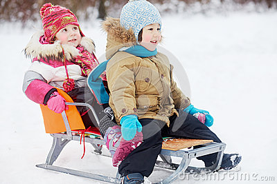 Two little children sit in sled