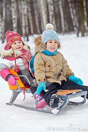 Two little children sit in sledge