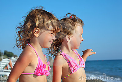 Two little girls on beach, Looking afar