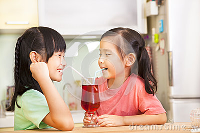 Two little girls drinking juice at home