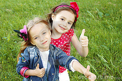 Two little girls friends. Thumbs up