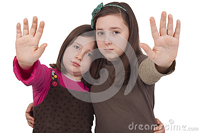 Two little girls gesturing stop