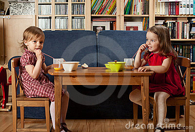 Two little girls have a breakfast at home