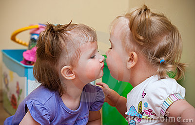 Two little girls kissing