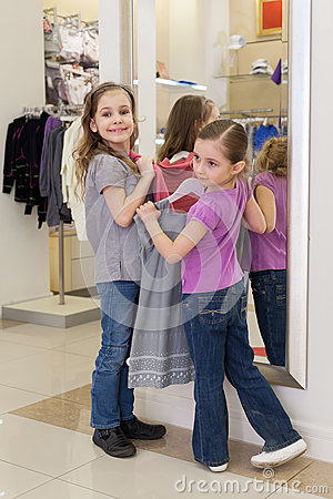 Two little girls near a mirror try on clothes in a store