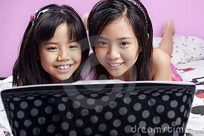 Two little girls playing with laptop