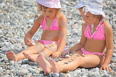 Two little girls is playing with pebble stones