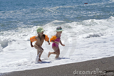 Two little girls plays at the seaside