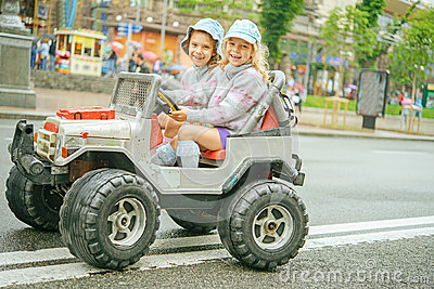 Two little girls riding toy car