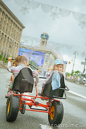 Two little girls riding toy cycle