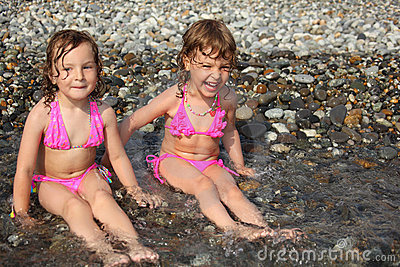 Two little girls sit ashore in water