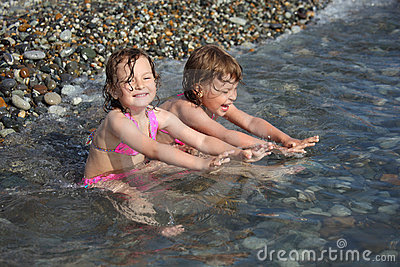 Two little girls sit  in sea