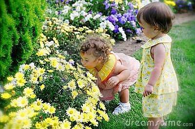 Two Little Girls Smelling Spring Flowers