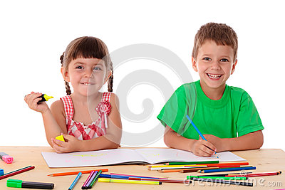 Two little kids draw with crayons