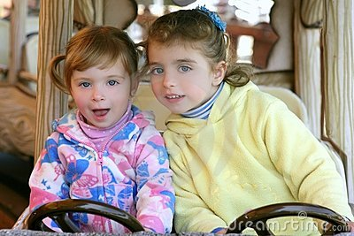 Two little sister girls driving car on fairground