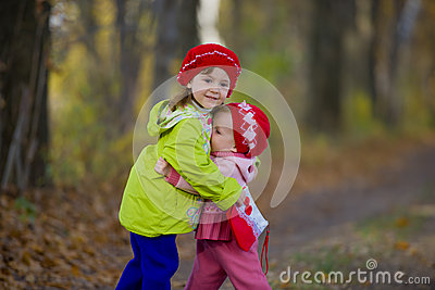 Two little sisters embrace each other