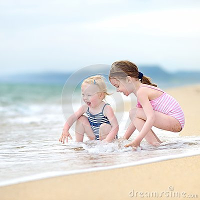 Free Two Little Sisters Having Fun On A Beach Royalty Free Stock Images - 46003649