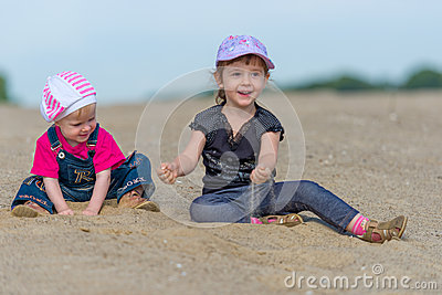 Two little sisters playing in the sand on the beac