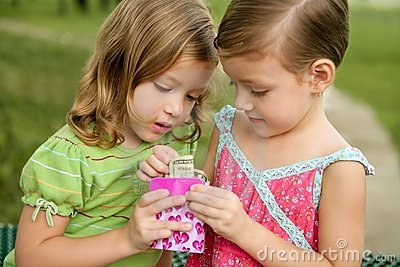 Two little twin girls find a dollar note