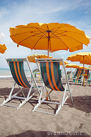 Two lounges and yellow umbrella on the beach