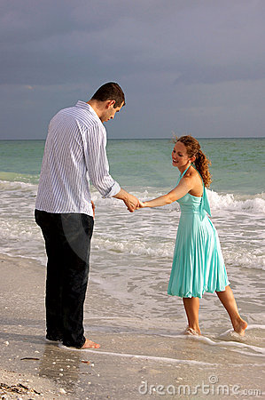 Two lovers holding hands and talking at the beach