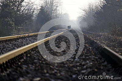 Two lovers holding hands walking on the train tracks
