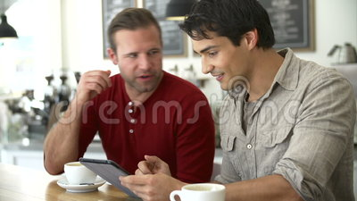 Two Male Friends In Coffee Shop Looking At Digital Tablet. Two male friends sitting at table in café looking at digital tablet. Shot on Sony FS700 in PAL format stock video