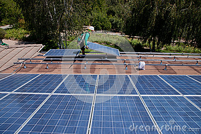 Two male solar workers install solar panels Editorial Photography