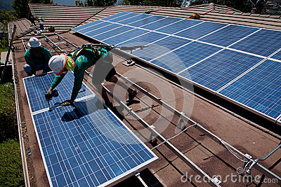 Two male solar workers install solar panels Editorial Stock Photo