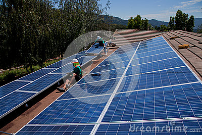 Two male solar workers install solar panels Editorial Image
