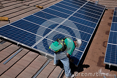 Two male solar workers install solar panels Editorial Photo