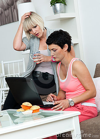 Two mature woman friends with laptop at home
