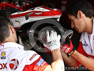 Two mechanics change the exhaust pipe Editorial Stock Image