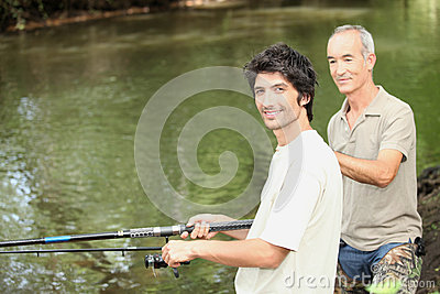 Two men angling beside river