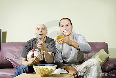 Two men drinking beer and watching soccer on tv
