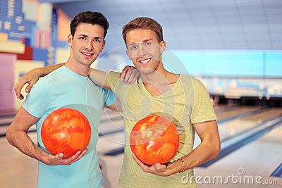 Two men embrace and hold balls in bowling club